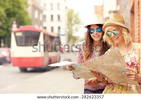 A picture of two girl friends using a map in the city - stock photo