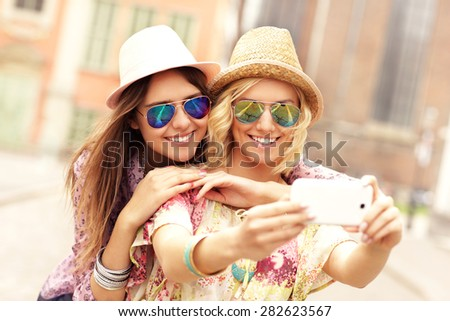 A picture of two happy girl friends taking selfie in the city - stock photo