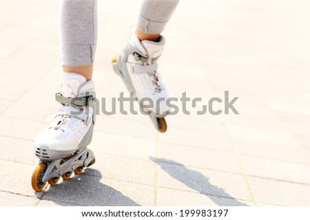 A picture of woman's legs with roller blades on the path - stock photo