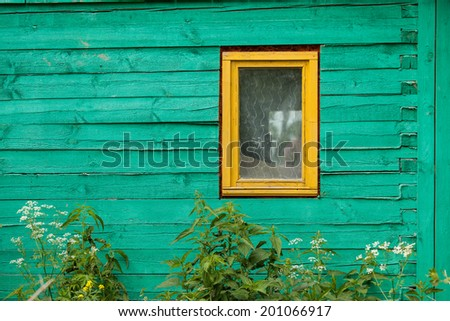 A picturesque and bright green wall with a wooden yellow window - stock photo