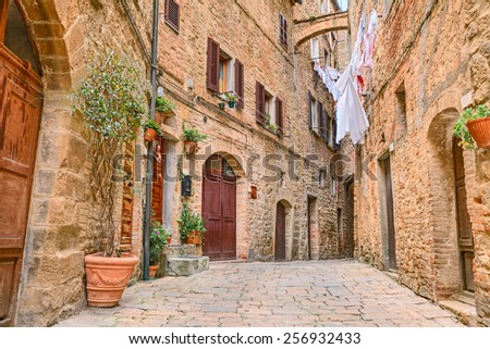 a picturesque typical corner with clothes hanging in the old town of Volterra, Tuscany, Italy  - stock photo