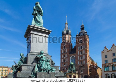 A piece of Adam Mickiewicz statue with a Mariacki church in the background on main Market Square in Cracow, Poland - stock photo