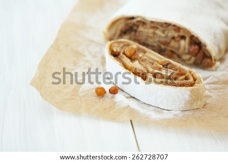 a piece of apple strudel on baking paper on a light wooden background - stock photo