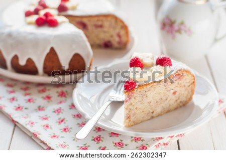 A Piece of Banana Cake with Sugar Glaze Topped with Raspberries and Banana Slices, copy space for your text, shallow dof - stock photo