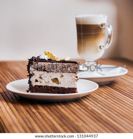 A piece of chocolate cake on a plate, coffee in the background - stock photo