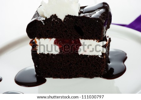 A piece of chocolate cake with white cream chocolate sauce and strawberry filling on white plate - stock photo