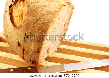 A piece of homemade bread with a knife to cut - stock photo
