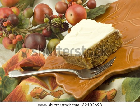 A piece of homemade carrot cake with cream cheese frosting on a fall leaf plate with fall decorations, horizontal with copy space - stock photo