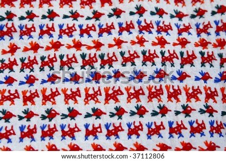 A piece of Mexican handmade fabric with animal and bird motives stitched on it - stock photo
