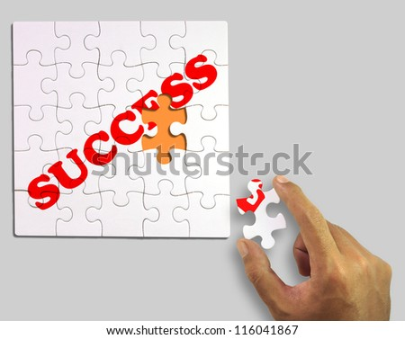 A piece of puzzle in hand. to complete the word success (Clipping Path) - stock photo