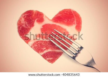 A piece of raw meat in the form of heart and a silver fork. Toned - stock photo