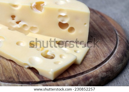 A pieces of  tasty cheese with big holes on the wood plank - stock photo