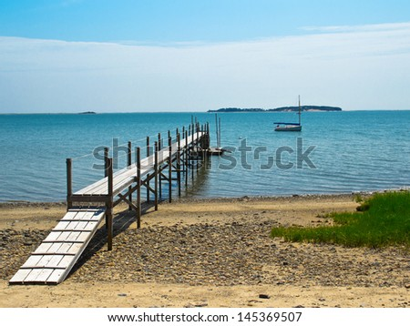 A pier juts out from Pleasant Bay beach near Chatham, MA, on Cape Cod. - stock photo