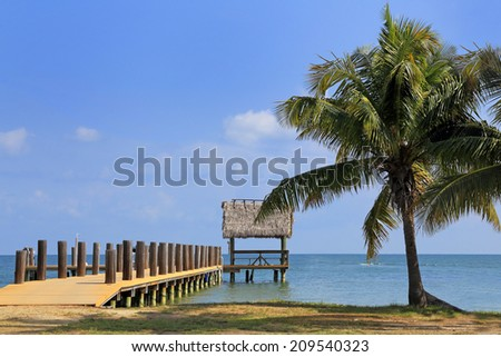A pier on a tropical island leads out to a small thatched-roof structure in this inviting travel image. - stock photo