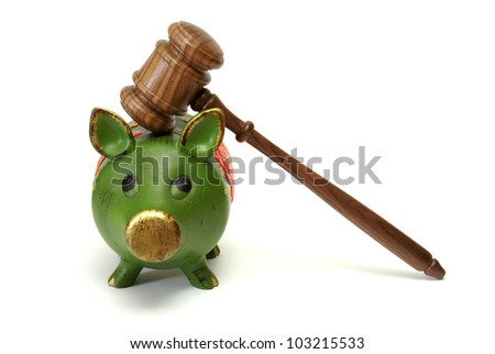 A pig bank and a mallet represent legal expense concepts. - stock photo