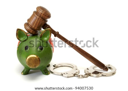 A pig bank, handcuffs, and a mallet represent legal expense concepts. - stock photo