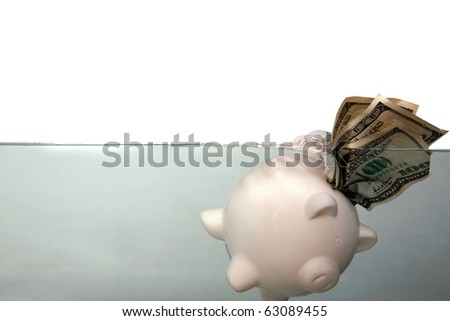 a piggy bank floats in dark murkey water, representing the idea of drowning in debt, or keeping your head above water and other financial concepts - stock photo