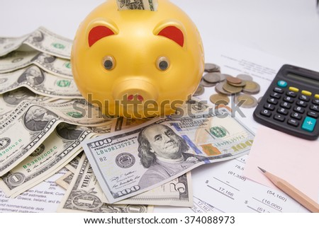 A piggy bank with money dollars and calculator  on financial report, savings - stock photo