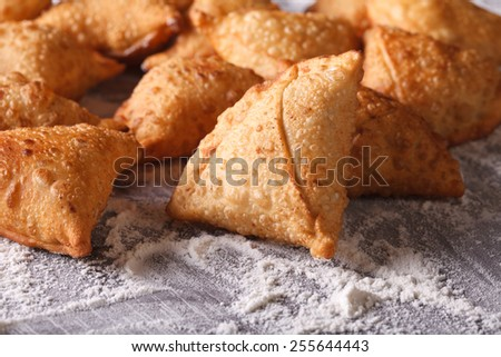 A pile of baking samosas on a floured table. Horizontal close-up  - stock photo