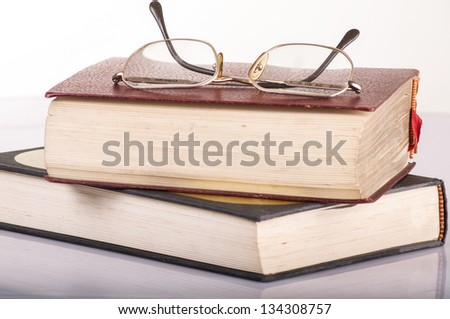 a pile of books and glasses symbolizing the concept of reading habit or studying - stock photo