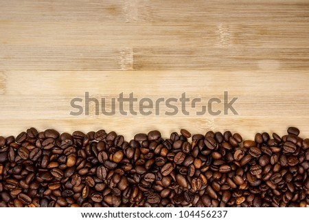 A pile of coffee beans forming a simple stripe frame on a natural background. - stock photo