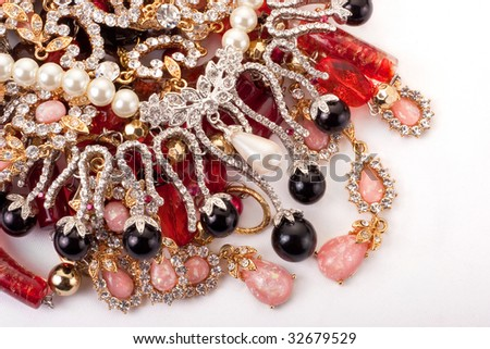 A pile of colored jewelry on white background - stock photo