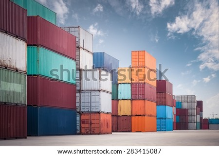 a pile of container in freight yard against a blue sky, transport background - stock photo