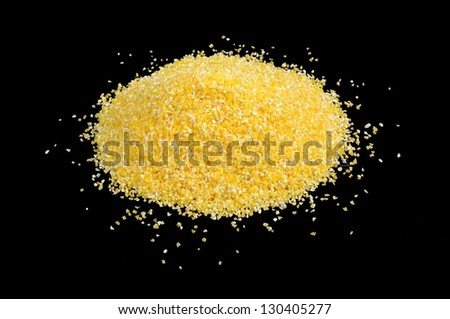 A pile of corn grits on a black background - stock photo