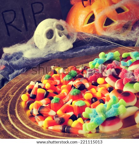 a pile of different Halloween candies with scary ornaments in the background, such a tombstone, a skull, a pumpkin and cobwebs - stock photo
