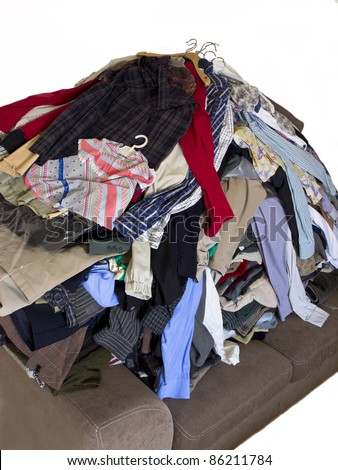A pile of dirty laundry. Many clothes on bed - stock photo