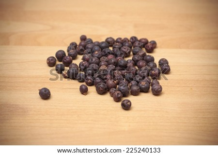 A pile of dried juniper berries on a wooden background - stock photo