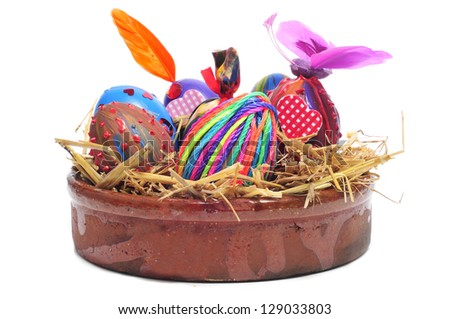 a pile of easter eggs painted in different colors and patterns in a earthenware bowl with straw, on a white background - stock photo