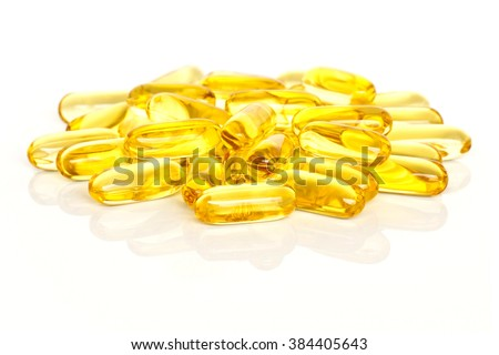 A pile of fish oil supplement capsules isolated on a white background. - stock photo