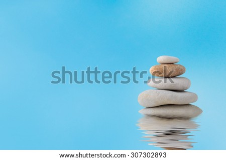 A pile of five stacked stones with a watery rippled reflection below and blue sky with light white cloud haze in the background. - stock photo