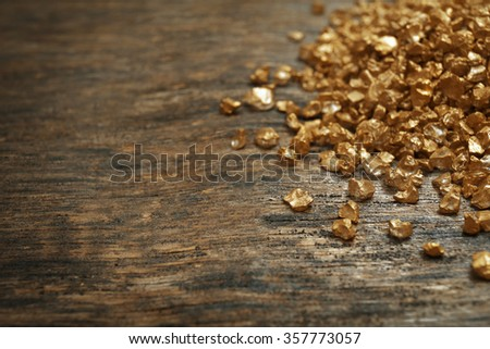 A pile of Gold nugget grains, on wooden background - stock photo