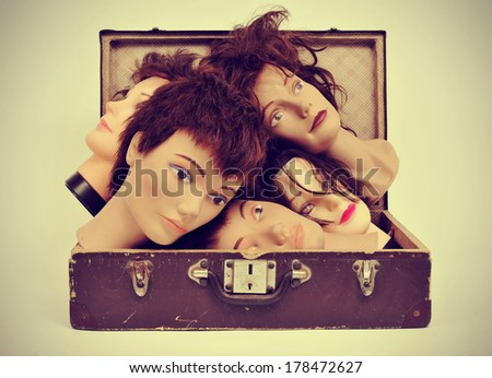 a pile of mannequin heads in an old suitcase with a retro effect - stock photo
