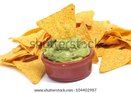 a pile of nachos and a bowl with guacamole on a white background - stock photo