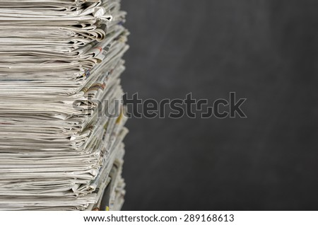 A pile of newspapers in front of a blackboard - stock photo