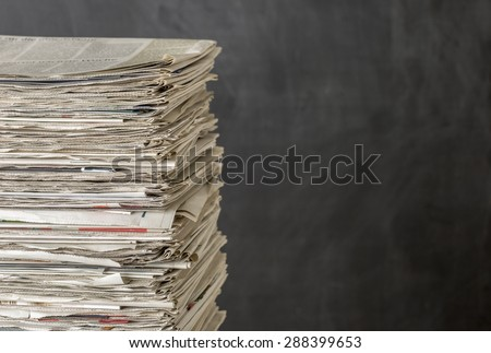 A pile of newspapers on a dark background - stock photo