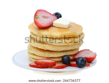 a pile of pancakes with fresh fruits on plate isolated on white  - stock photo