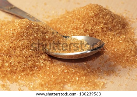A pile of raw brown sugar with a spoon on a table - stock photo