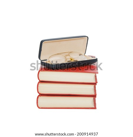 A pile of red books, glasses and case of glasses isolated on white background - stock photo