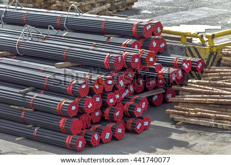 A pile of round and square metal pipes, chocks , packed in stacks with tags size parameters for cranes and transport of cargo ships in the seaport and railway wagons - stock photo