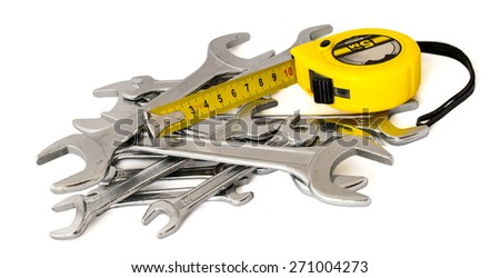 A pile of spanners, wrenches, keys and roulette, tape, tape-measure, tape-line, reel on a white background - stock photo
