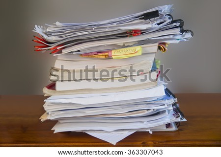 A pile of study books and papers on a wooden desk. Some books have sticky notes hanging out from them. Spiral notebooks and paper clips.  - stock photo