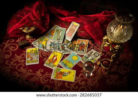 A pile of tarot cards lie scattered and spread across a table top surrounded by multiple occult items. - stock photo