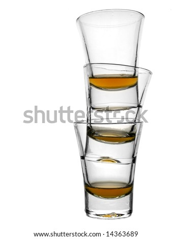 A pile of three almost empty shots of whiskey on white background. - stock photo