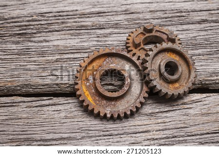 A pile of three rusty gears sits on a rustic wooden background. - stock photo