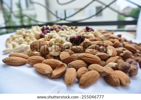 A pile of various nuts - almonds, cashews and hazelnuts, and dried cranberries. Healthy/clean eating concept. - stock photo