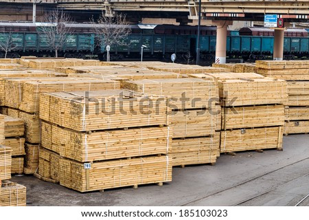 A pile of wood edged boards packed in stacks with tags size parameters for loading cranes and transport the cargo ships in the seaport and railway wagons  - stock photo
